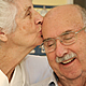 Elder woman kissing smiling husband on forehead.